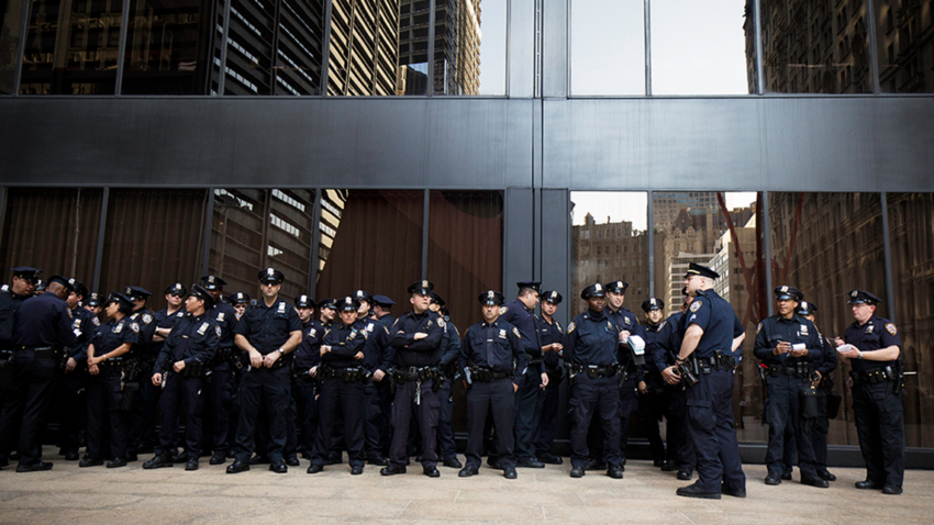 Police officers gather in front of a building. Photo by Felix Koutchinski on Unsplash